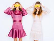 Jeunes belles amies drôles de mode avec la tranche orange sur le fond blanc Maquillage et coiffure Ayez l'amusement et dupez Photos stock