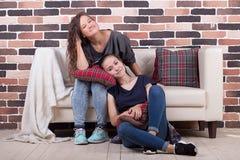 Jeunes belles amies s'asseyant sur le divan et le sourire Photo stock