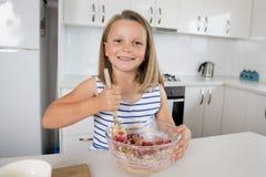 Jeunes belles et adorables années de la fille 6 ou 7 faisant cuire et faisant à la maison la cuisine cuire au four préparant le g Photos libres de droits