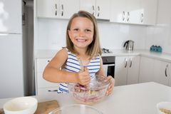 Jeunes belles et adorables années de la fille 6 ou 7 faisant cuire et faisant à la maison la cuisine cuire au four préparant le g Images stock