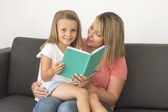 Jeunes belles et heureuses femmes s'asseyant ainsi que ses 7 années adorables de fille de livre de lecture blond adorable appréci Photo stock
