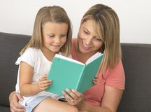 Jeunes belles et heureuses femmes s'asseyant ainsi que ses 7 années adorables de fille de livre de lecture blond adorable appréci Image libre de droits