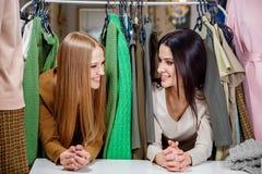 Jeunes belles femmes au magasin de tissu Meilleurs amis partageant le temps gratuit ayant l'amusement et faisant des emplettes au Photo stock