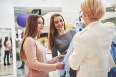 Jeunes belles femmes au marché hebdomadaire de tissu Le directeur de magasin aide l'acheteur Meilleurs amis partageant le temps l photo libre de droits