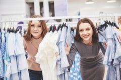 Jeunes belles femmes au marché hebdomadaire de tissu - meilleurs amis partageant le temps gratuit ayant l'amusement et faisant de photos libres de droits