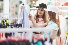 Jeunes belles femmes au marché hebdomadaire de tissu - meilleurs amis partageant le temps libre ayant l'amusement et l'achat photos libres de droits