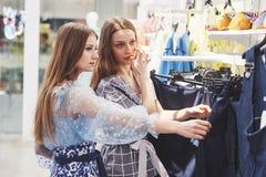 Jeunes belles femmes au marché hebdomadaire de tissu - meilleurs amis partageant le temps libre ayant l'amusement et l'achat photos stock