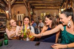 Jeunes belles femmes avec des cocktails dans la barre ou le club Image stock