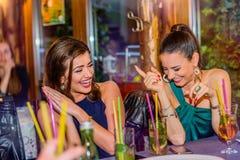 Jeunes belles femmes avec des cocktails dans la barre ou le club Photographie stock