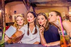 Jeunes belles femmes dans la barre prenant le selfie Image stock
