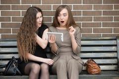 Jeunes belles femmes regardant l'écran de comprimé dans le choc Photographie stock libre de droits