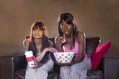 Jeunes belles femmes regardant la télévision avec le maïs éclaté Photographie stock libre de droits