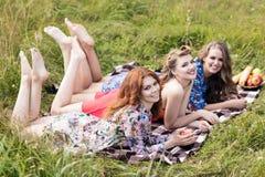 Jeunes belles femmes se trouvant sur le plaid en parc d'été Images stock