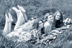 Jeunes belles femmes se trouvant sur le plaid en parc d'été Photo stock
