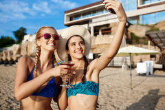 Jeunes belles filles dans le sourire de vêtements de bain, faisant le selfie à la plage Photographie stock libre de droits