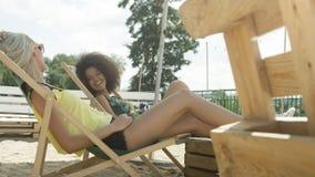 Jeunes belles filles de métis s'asseyant sur des lits pliants sous le parapluie et appréciant des vacances Images stock