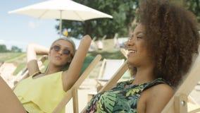 Jeunes belles filles de métis s'asseyant sur des lits pliants sous le parapluie et appréciant des vacances Image stock