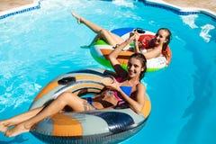 Jeunes belles filles souriant, prenant un bain de soleil, détente, nageant dans la piscine Images stock