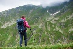 Jeunes belles montagnes rocheuses neigeuses admiratives de touristes femelles couvertes de brouillard épais en Roumanie photos stock