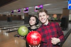 Jeunes belles paires posant avec des boules sur le bowling Bowling de jeu de jeune homme et de fille Photo stock