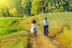 Jeunes bicyclettes de tour de couples dans le pré Images libres de droits