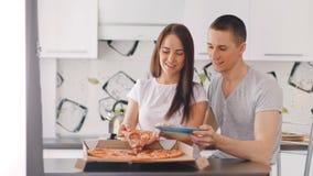 Jeunes boîte d'ouverture de couples et pizza heureuses de mise au plat banque de vidéos