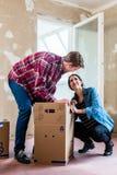 Jeunes boîtes d'ouverture de couples pendant la rénovation de la nouvelle maison après m photographie stock