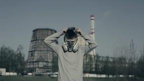 Jeunes boyis toussant et portant le masque de pollution contre des cheminées d'usine Le garçon suffoque en raison de la pollution banque de vidéos