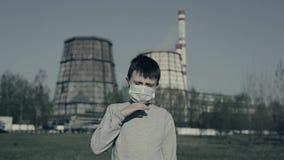 Jeunes boyis toussant et portant le masque de pollution contre des cheminées d'usine Le garçon suffoque en raison de la pollution clips vidéos