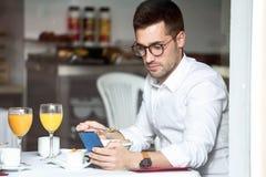 Jeunes céréales mangeuses d'hommes belles tout en textotant avec son téléphone portable dans la salle à manger de l'hôtel photos libres de droits