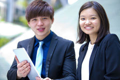Jeunes cadres commerciaux asiatiques discutant à l'aide de la tablette images stock