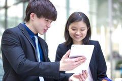 Jeunes cadres commerciaux asiatiques marchant et discutant à l'aide de la tablette Photos stock
