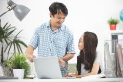 Jeunes cadres heureux asiatiques, employés discutant le nouveau projet photographie stock