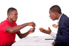 Jeunes cartes de jeu heureuses d'hommes à la table de jeu image libre de droits