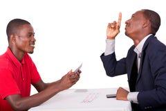 Jeunes cartes de jeu heureuses d'hommes à la table de jeu photos libres de droits