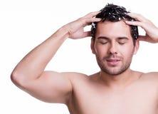 Jeunes cheveux de lavage de sourire heureux d'homme. Photos libres de droits