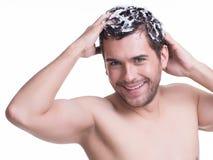 Jeunes cheveux de lavage de sourire heureux d'homme Photographie stock