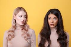 Jeunes choqués deux dames se tenant au-dessus du fond jaune Image libre de droits