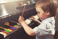 Jeunes clés de piano de peinture de garçon Beaux-arts et musique Image stock
