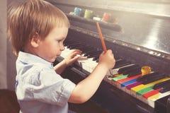 Jeunes clés de piano de peinture de garçon Beaux-arts et musique Art vrai Image stock
