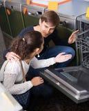 Jeunes clients choisissant la nouvelle machine à laver la vaisselle dans l'appareil s Photographie stock