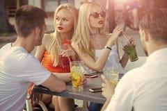 Jeunes cocktails de boissons d'amis dans la barre de salon Photographie stock libre de droits