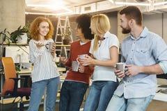 Jeunes collègues appréciant la pause-café dans le bureau moderne photo stock