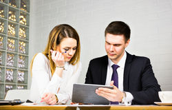 Jeunes collègues d'affaires discutant le travail sur un ordinateur portable dans l'espace de Co-travail, hommes d'affaires d'entr Image stock