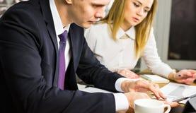 Jeunes collègues d'affaires discutant le travail sur un ordinateur portable dans l'espace de Co-travail, hommes d'affaires d'entr Photo libre de droits