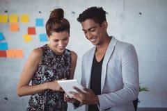 Jeunes collègues de sourire d'affaires travaillant ensemble sur le comprimé numérique Image stock