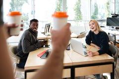 Jeunes collègues de sourire s'asseyant dans le bureau coworking Photos stock