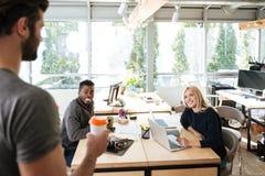 Jeunes collègues heureux s'asseyant dans le bureau coworking Photo stock