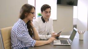 Jeunes collègues parlant tout en se reposant à la table avec l'ordinateur portable et le comprimé à la société clips vidéos