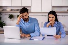 Jeunes collègues préoccupés d'affaires s'asseyant à la table images stock